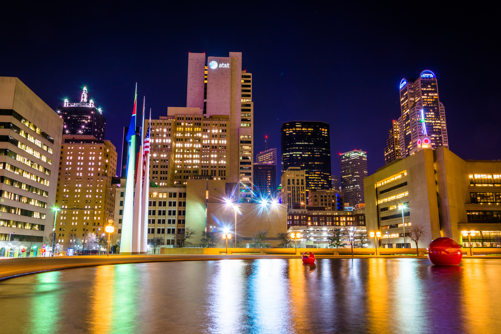 The Dallas skyline and the reflecting pool at City Hall at night, in Dallas, Texas.