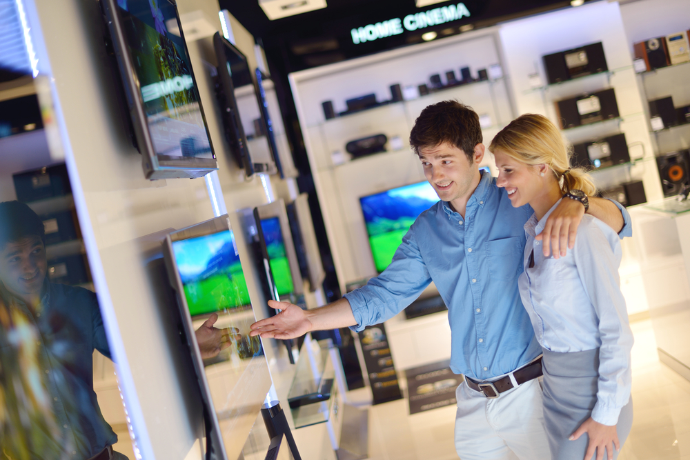 people in consumer electronics  retail store looking at latest laptop, television and photo camera to buy-1